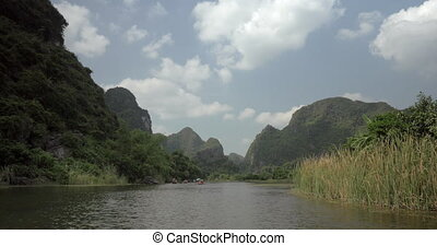 Trang an bai in Hanoi, Vietnam on a scenic river sailing boat with tourists