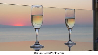 Woman and man hands are clinking glasses of champagne on sunset sea background, close up view