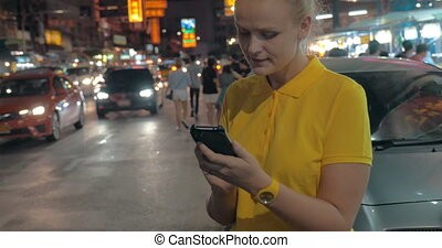 Woman with mobile at the roadside of night Bangkok, Thailand...