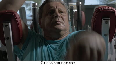 Grown man in blue shirt in the gym performing exercises on...