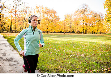 Woman jogging and listening music - Young woman with...