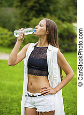 Portrait of young beautiful dark haired woman drinking water...