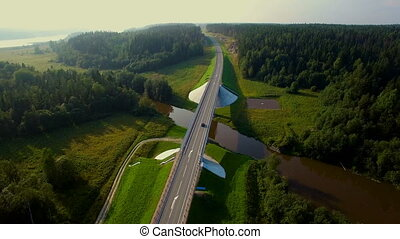 aerial view of cars going over the bridge in the forest -...