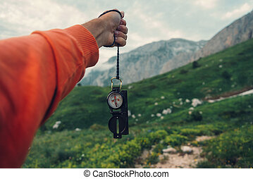 Tourist with compass in mountains