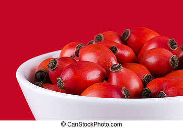 Rose hips in a white bowl on red
