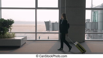 Woman chatting on mobile phone in airport terminal - Woman...