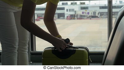 Woman weighing luggage with hand scales - Woman using hand...