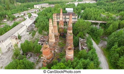 Ruins of old factory with high chimney - aerial view of an...