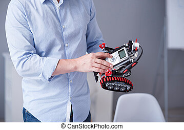 Mans fingers pressing buttons on a robot - Technology of...