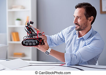 Happy scientist observing his robot invention - New...
