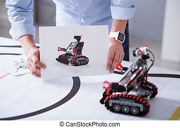 Both image and a real toy robot - Compare. Male hands...