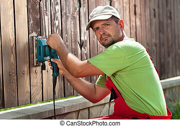 Worker polishing old wooden fence with power tool - a vibrating sander
