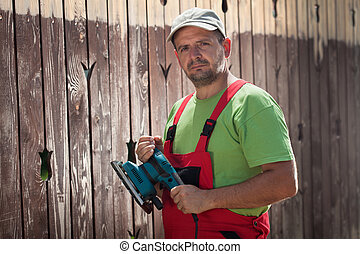 Male worker with vibrating sander in front of old wooden fence