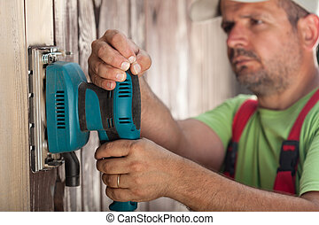Worker scraping vertical wooden surface with vibrating sander - closeup
