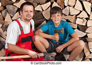 Man and boy sitting together in front of chopped wood