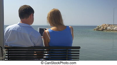 Young woman and man are sitting on bench on beach on sea...