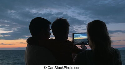 At sunset family photographed on tablet in city Perea, Greece.