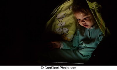 Little girl using tablet pc under blanket at night.