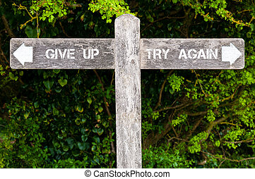 GIVE UP versus TRY AGAIN directional signs - Wooden signpost...
