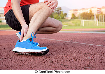 Runner with injured ankle on the track