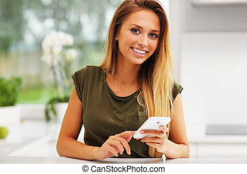 Young woman on the phone in kitchen