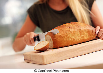 Woman slicing loaf of bread