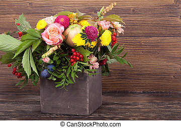 Amazing autumn bouquet with berries in a wooden vase on...