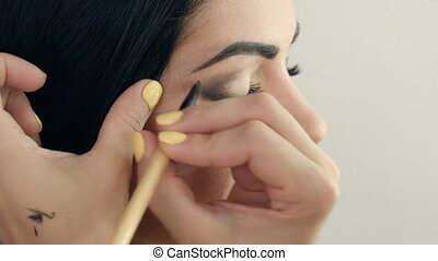Make-up artist applying makeup to model's eye. Close up...