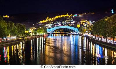 Tbilisi downtown. peace bridge made from glass, river...