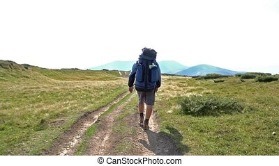 Tourist walking in mountains - Tourist man with big backpack...