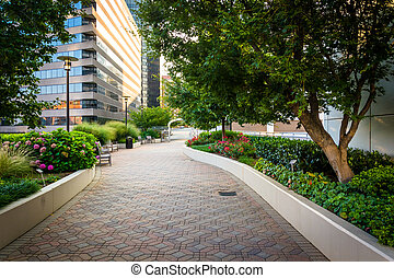 Gardens and modern buildings along a path at Freedom Park,...