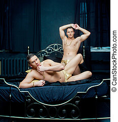 two men in bed - attractive men wearing golden chain and...