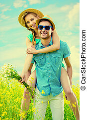 playful summer mood - Happy young people in love on a meadow...