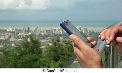 A modern city with high-rise buildings and ordinary homes. A man checks the messages on the phone in the foreground. Close-up. The forest and the sea behind