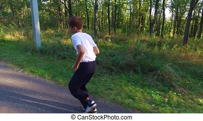 Slim teenager boy is running on paths and trails in the...