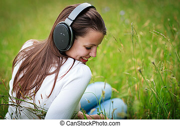 portrait of a pretty young woman listening to music on her...