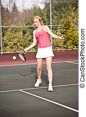 Tennis player - A beautiful caucasian tennis player hitting...