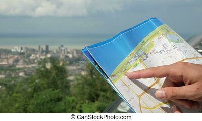 A modern city with high-rise buildings and ordinary homes. A man checks the route on a paper map. The forest and the sea behind