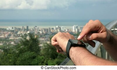 A modern city with high-rise buildings and ordinary homes. A man checks the messages on the smart watch in the foreground. Close-up. The forest and the sea behind