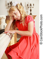 Girl sitting at the piano - Dreaming little girl in a long...