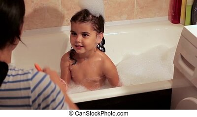 Curly girl bathes in a bath with foam. Draws a multi-colored pencils on a bath. Mother and daughter engaged. creation