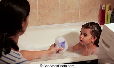 Beautiful girl bathing in a bath with foam. Blowing the foam. She laughs, has fun with her mother. play toys.