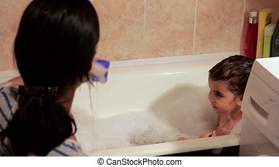Beautiful girl bathing in a bath with foam. She laughs, has fun with her mother. play toys. cup of water is poured