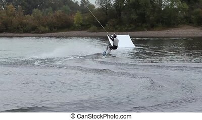 man on a wakeboard doing a back flip from a springboard. Beautiful and dangerous stunt. wakepark