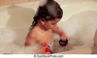 The girl bathes in a bath with foam. Playing with toys. Water treatments before bedtime