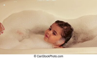 Curly girl bathes in a bath with foam. Learn to swim. Water treatments.