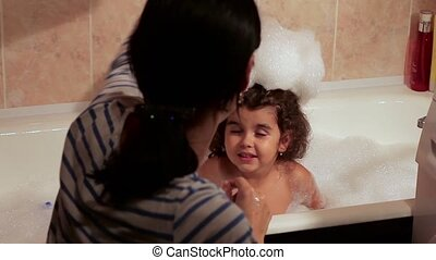 Beautiful curly-haired girl bathing in the bath with foam. Foam on the head. Fun, enthusiasm