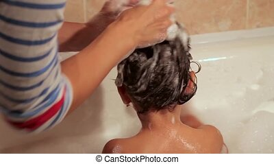 Mother washes her daughter shampoo. Curly, thick, beautiful hair. Mother bathes beautiful daughter in the bath with foam. Back view