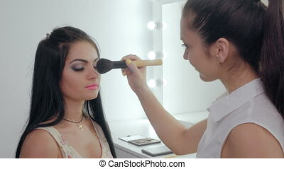 makeup artist doing makeup for the beautiful brunette a...