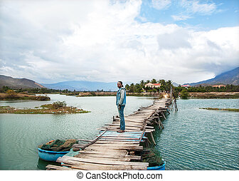 brutal man stands on the bridge,around it is very beautiful.